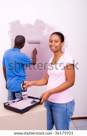 young african american couple painting house - stock photo