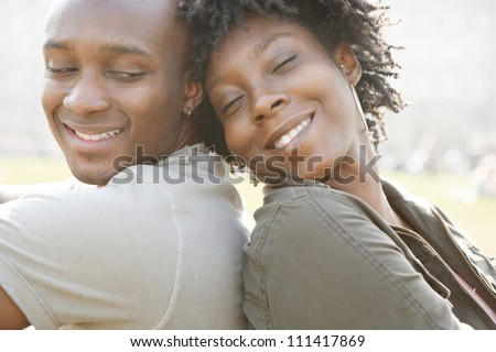 Young african american couple sitting back to back while visiting London on vacation, smiling and in love.