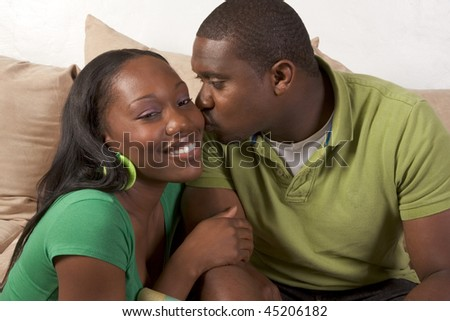 Young African American couple sitting in living room on couch enjoying time together - stock photo