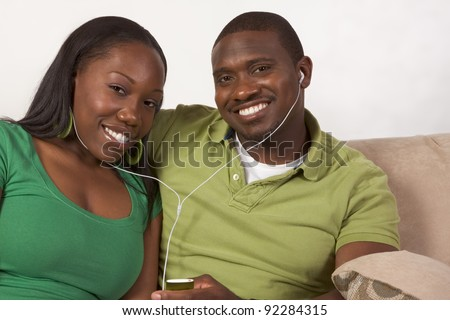 Young African American couple sitting in living room on couch enjoying time together and share usage of portable MP3 player, using the same headphones - stock photo