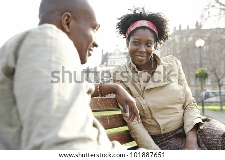 Young african american couple sitting on a bench in a park in the city of London.