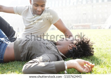 Young african american couple talking as they relax laying down on green grass in the city of London, while on vacations.