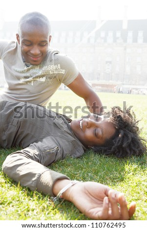 Young african american couple talking as they relax laying down on green grass in the city of London, while on vacations. - stock photo