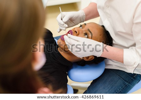 Young African-American ethnic black female opening mouth while dentist in white latex gloves and mask, his assistant check condition of her teeth - stock photo