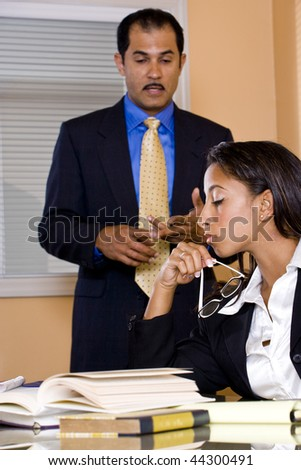 Young African-American female office worker reading papers in boardroom with middle-aged Hispanic businessman standing beside - stock photo