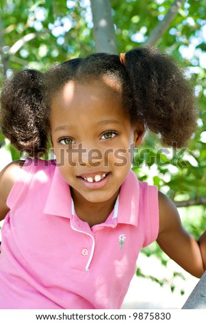 Young African-American Girl Playing in a Tree with Great Eye Contact - stock photo