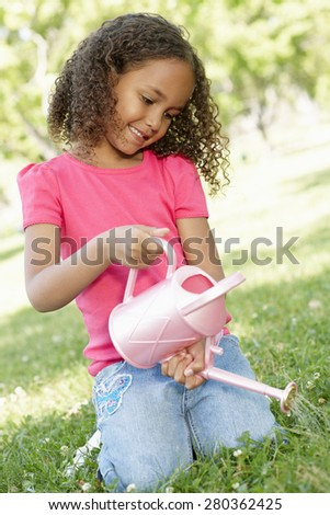 Young African American Girl With Watering Can In Park - stock photo