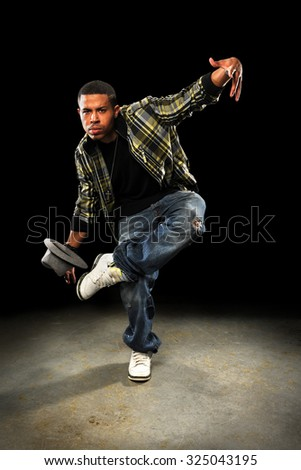 Young African American hip hop dancer performing over dark background