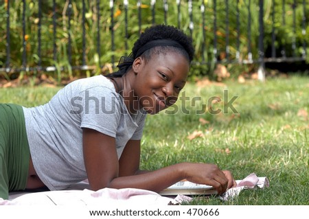Young  african american lady looks up from a book and smiles. - stock photo