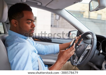 Young African American male driver using phone, in car view - stock photo