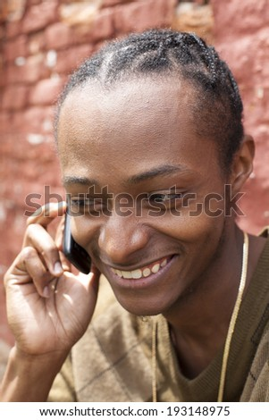 Young african american male smiling while on phone - stock photo