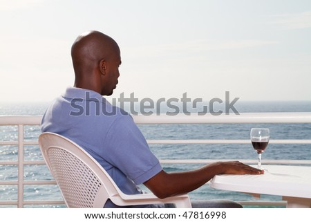 young african american man drinking wine on sea view balcony