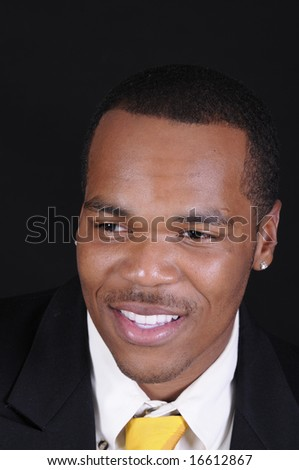 young African American man in a suit over a black background - stock photo