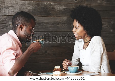 Young African American man in glasses drinking cappuccino with his beautiful girlfriend. Happy stylish friends having coffee together, sitting at a cafe, laughing and having a great time together - stock photo