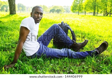 Young african american man in white shirt  with rucksack in a park - stock photo