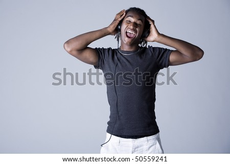 Young African American man listening to music on headphones and singing, studio shot - stock photo