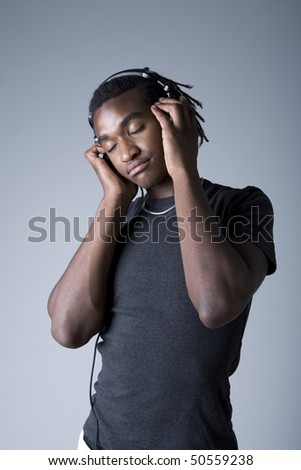 Young African American man listening to music on headphones, studio shot on gray background - stock photo