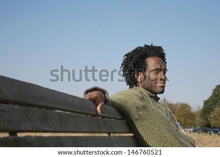 Young African American man listening to music while sitting on park bench - stock photo