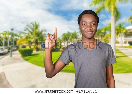 Young african american man pointing copy space - stock photo