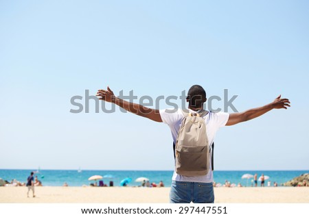 Young african american man standing with arms spread open at beach - stock photo