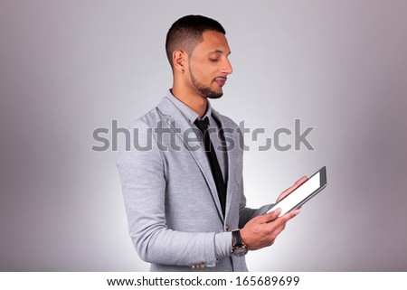 Young african american man using a tablet pc, over on gray background - Black people - stock photo