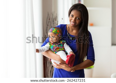 Young african american mother holding with her baby girl - stock photo