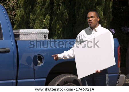 Young African American needing gas for truck with sign for your copy space - stock photo