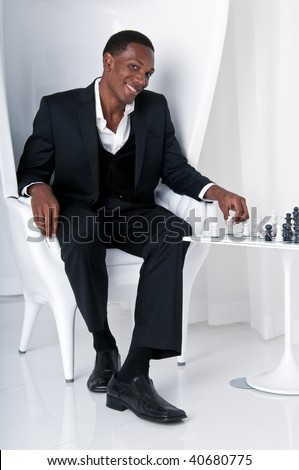 Young african American play chess in modern lounge. - stock photo