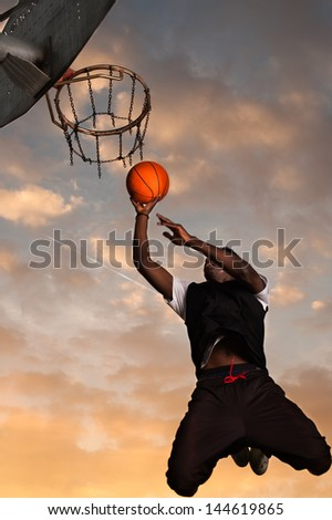 Young African-American player jumping to dunk during street basketball� match. It shows a spectacular sunset - stock photo