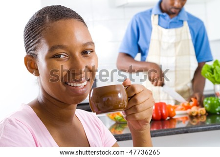 young african american wife relaxing at home, background is her husband cooking
