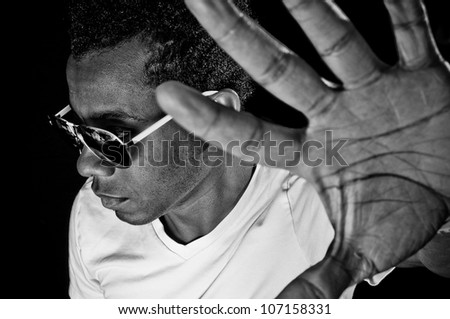 Young African American with his hand up looking away with focus on face - stock photo