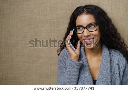 Young African American woman chatting on a mobile phone listening to the conversation with a smile, brown background with copy space - stock photo