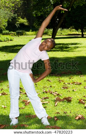 young african american woman doing exercise in garden - stock photo
