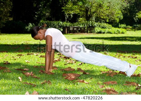 young african american woman doing push-ups in park - stock photo