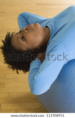 Young african american woman doing sit-ups on a pilates ball - stock photo