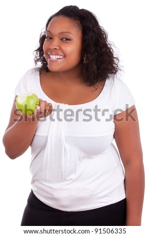 Young african american woman eating an  green apple, isolated on white background