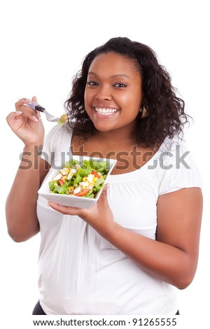 Young african american woman eating salad, isolated on white background - stock photo