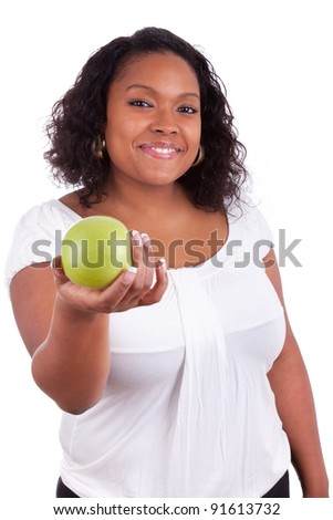 Young african american woman giving an  green apple, isolated on white background
