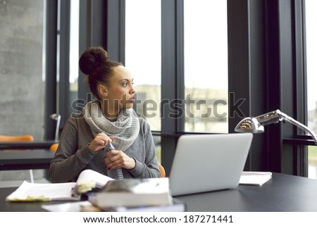 Young african american woman holding water bottle and looking away while studying in library. Female student sitting at table with laptop and books for study. Taking a break. - stock photo