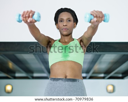 young african american woman in green sportswear doing weight lifting in fitness club. Horizontal shape, front view, waist up