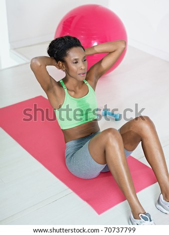 young african american woman in green sportswear exercising abdominals on pad in gym. Vertical shape, side view, full length