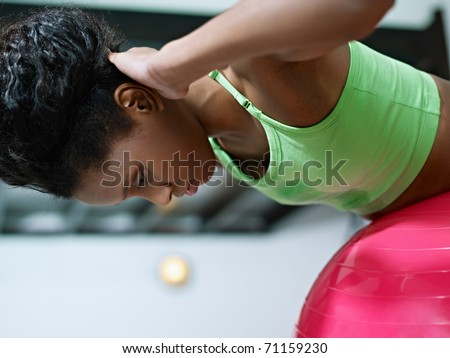 young african american woman in green sportswear exercising back muscles on fit ball in gym. Horizontal shape, side view, copy space - stock photo