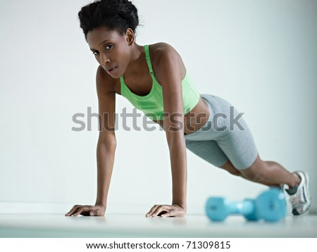 young african american woman in green sportswear exercising with pushups in fitness club, looking at camera. Horizontal shape, side view, copy space