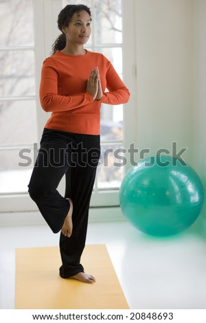 Young African American woman in yoga Tree pose at home - stock photo