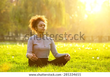 Young african american woman meditating in nature  - stock photo