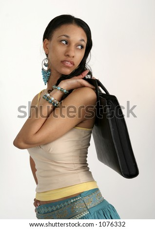 Young African American woman portfolio slung over her shoulder - stock photo