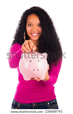 Young african american woman putting coin in piggy bank isolated - stock photo