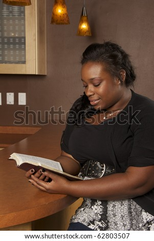 Young African American Woman Reading her Bible in a Cafe