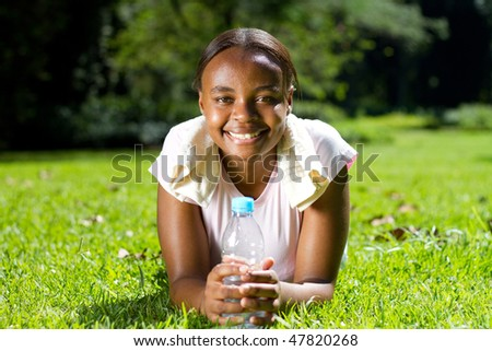 young african american woman relaxing on grass after doing fitness workout - stock photo