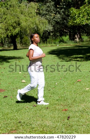 young african american woman running in park for exercise - stock photo